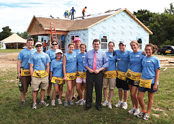 Part of the Pre-Orientation Program, first-year students worked on a local Habitat for Humanity project. They are pictured here with President Mark D. Gearan.