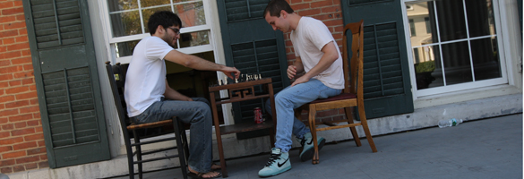 Members of the Kappa Alpha Society play chess on the porch